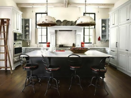 Open kitchen with industrial lighting, chairs, and ladder